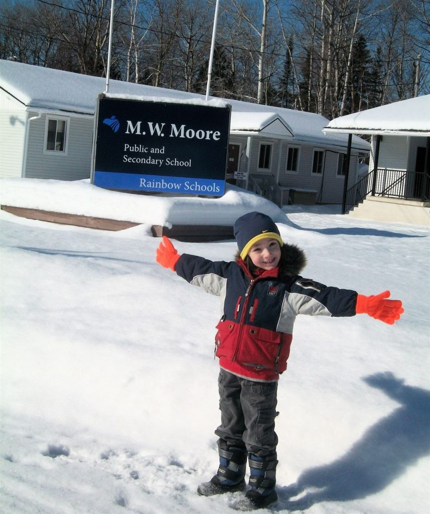 A child stands in front of the M.W. Moore Public and Secondary School