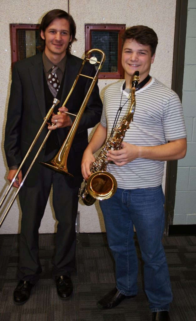 An image of a student and a teacher holding instruments