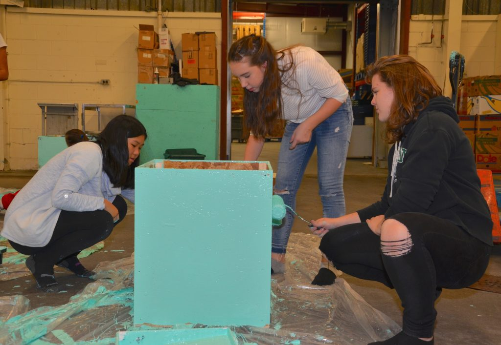 MacLeod students painting donation boxes