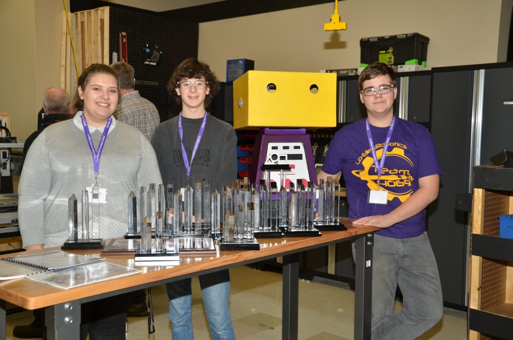 Three students standing with awards won by the FIRST Robotics team