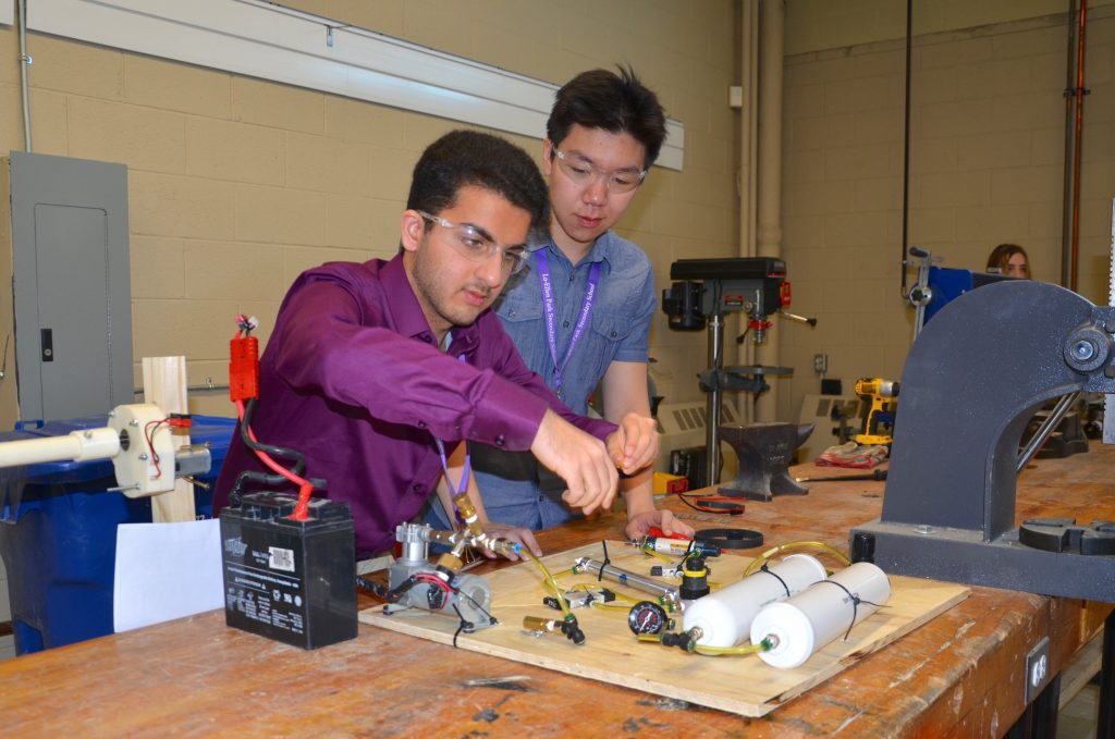 Two students working on pneumatics