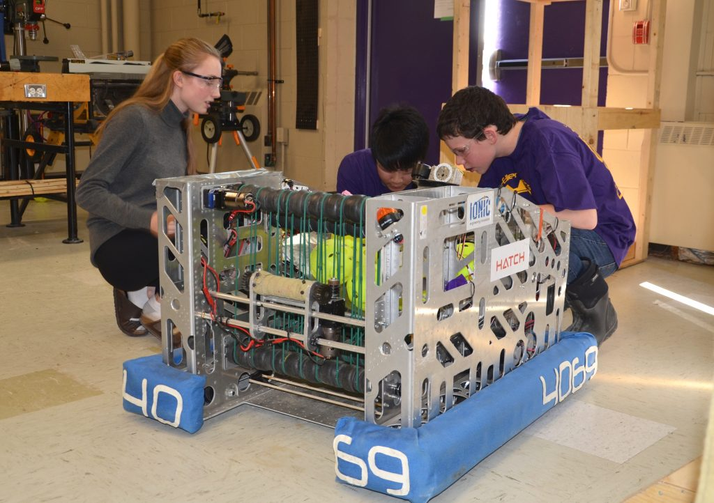 Three students working on the Lo-Ellen Park Robot