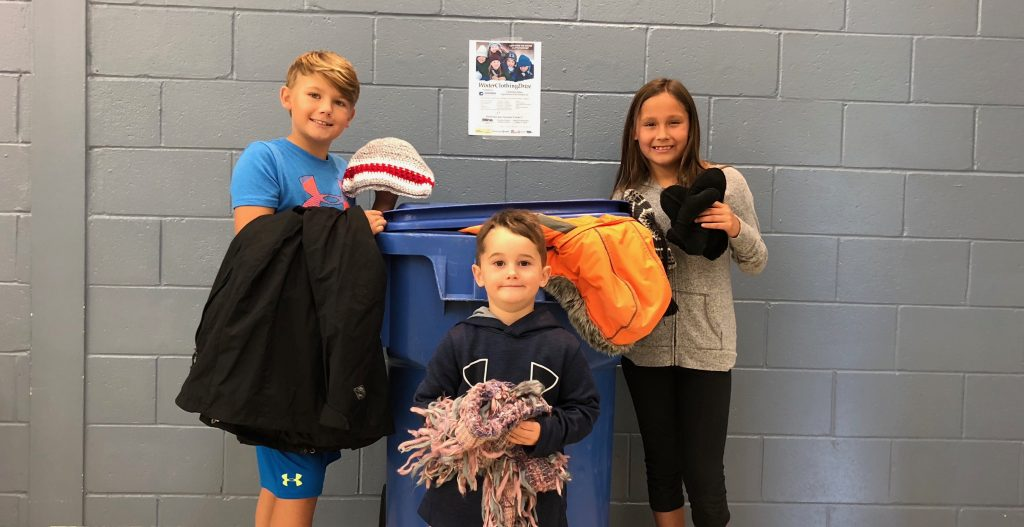 From left, Hayden Barton, Easton Sirkka and Sabrina Nootchtai of R.H. Murray Public School invite the community to drop off gently used winter clothing to any Rainbow School. The clothing will be redistributed to make this winter a little warmer.