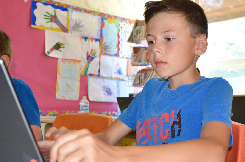 R.L. Beattie Public School student Jacob Paille completes an in-class assignment using a laptop.