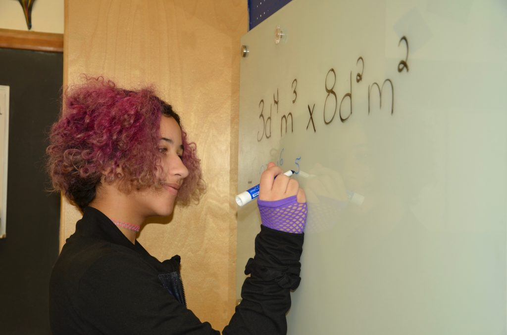 a student practicing math on a whiteboard